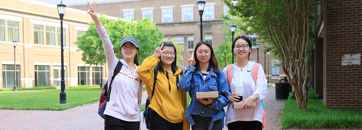Four students visiting the School of Education from China pose and smile, with the Oliver Hall Courtyard in the background.