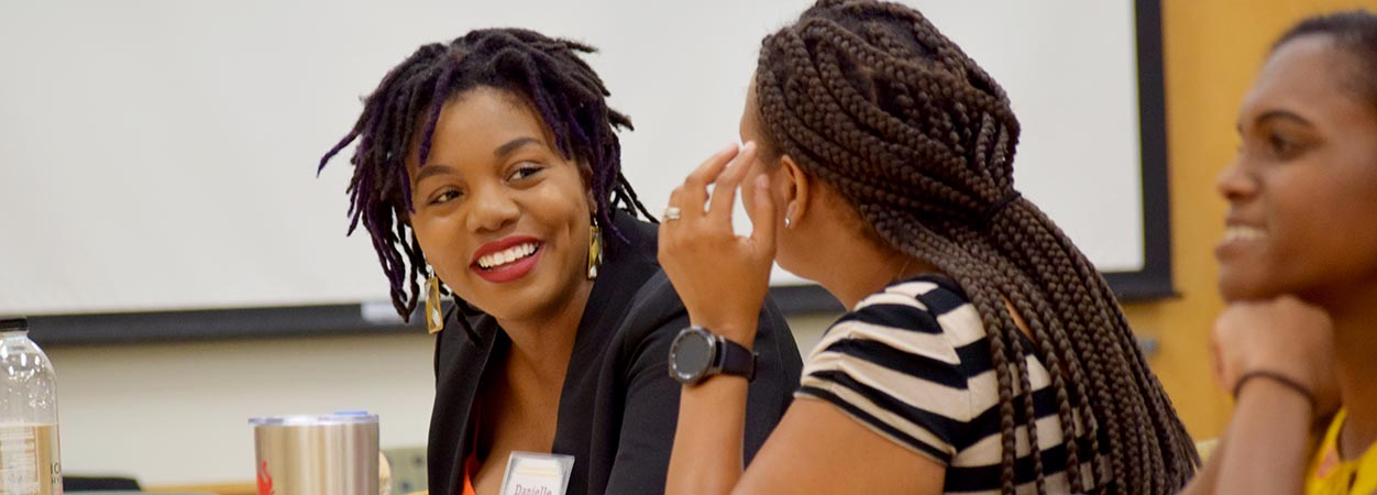 iCubed Visiting Scholar Dr. Danielle Apugo talks with a student between sessions at the VCU SOE Holmes Scholars Summit.