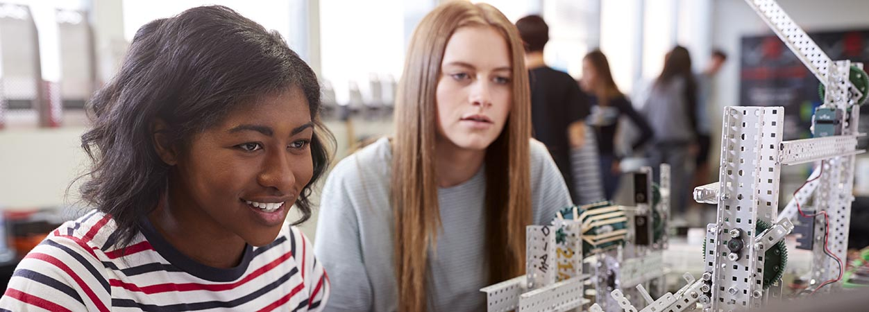 Two undergraduate students looking at an engineering project in the classroom.